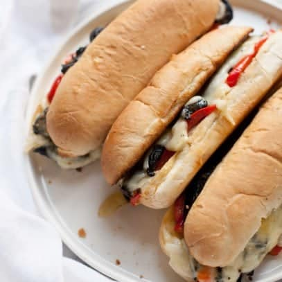 Overhead close-up shot of three portabella cheesesteaks on a white plate