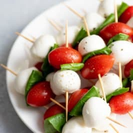 Side angle shot of Caprese Sticks on a white plate