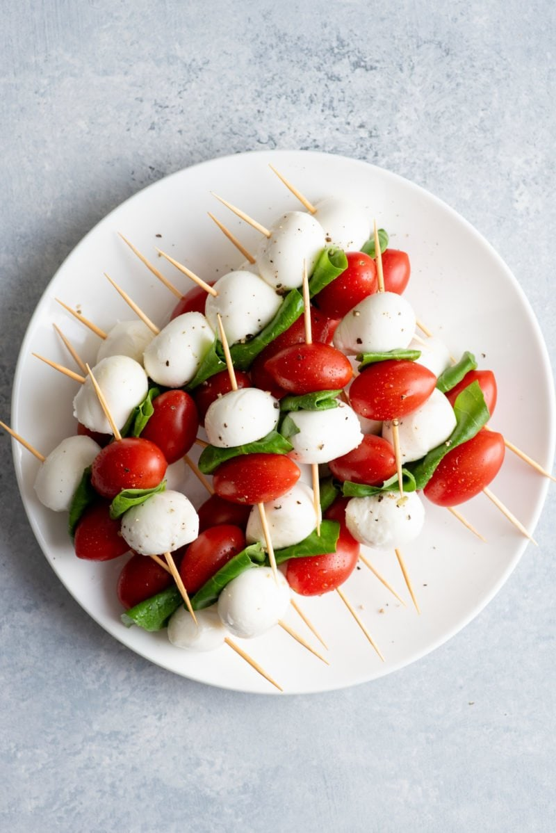 Overhead shot of Caprese Sticks on a white plate