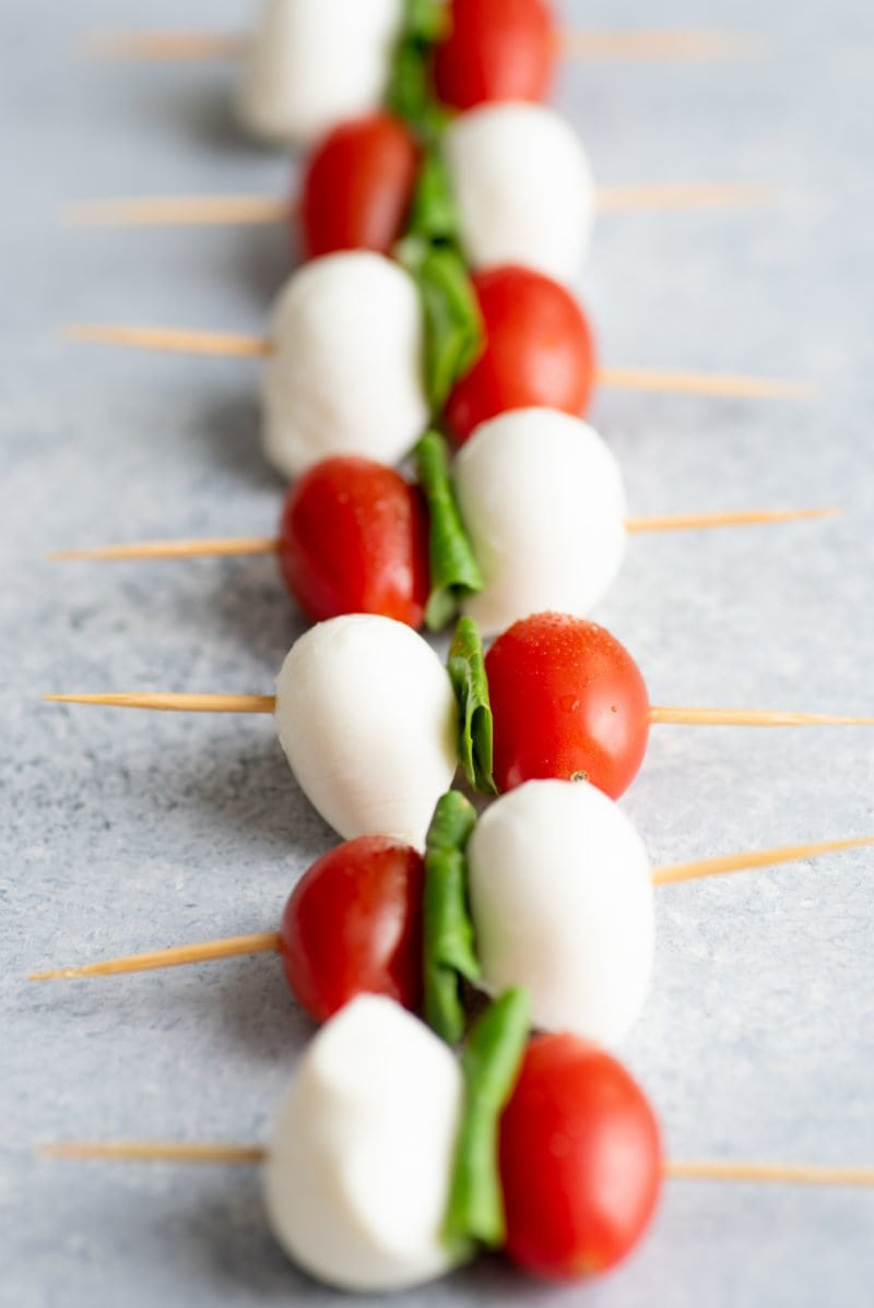 Side angle shot of Caprese Sticks lined up on a grey background
