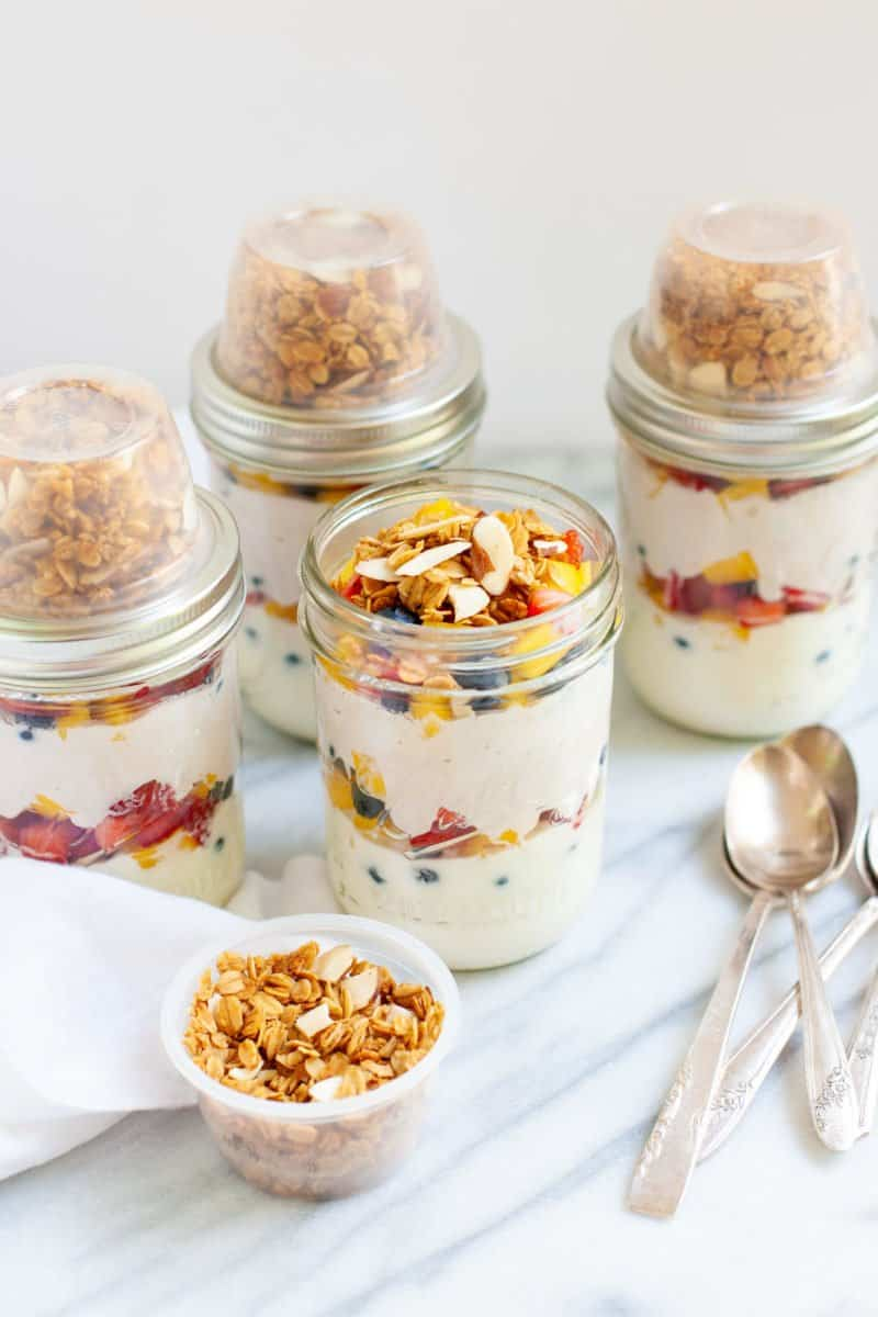 Side angle shot of prepared Meal Prep Fruit and Yogurt Parfaits in glass jars