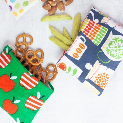 Three reusable snack bags, each spilling out a different snack - pretzels, almonds, and crispy snap peas