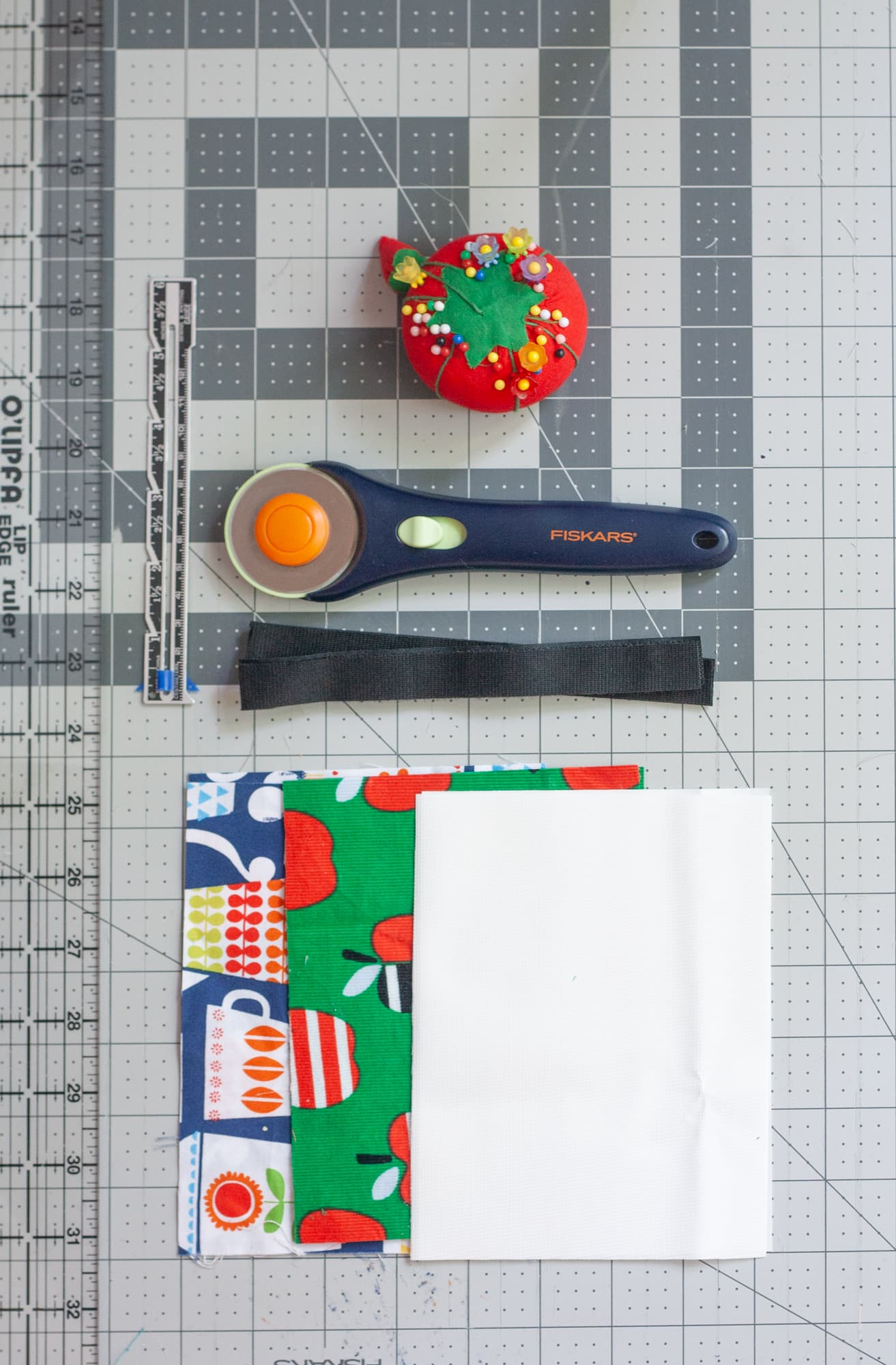 Sewing materials for reusable snack bags laid out on a cutting mat - rotary cutter, pin cushion, velcro, fabric, seam gauge, ruler