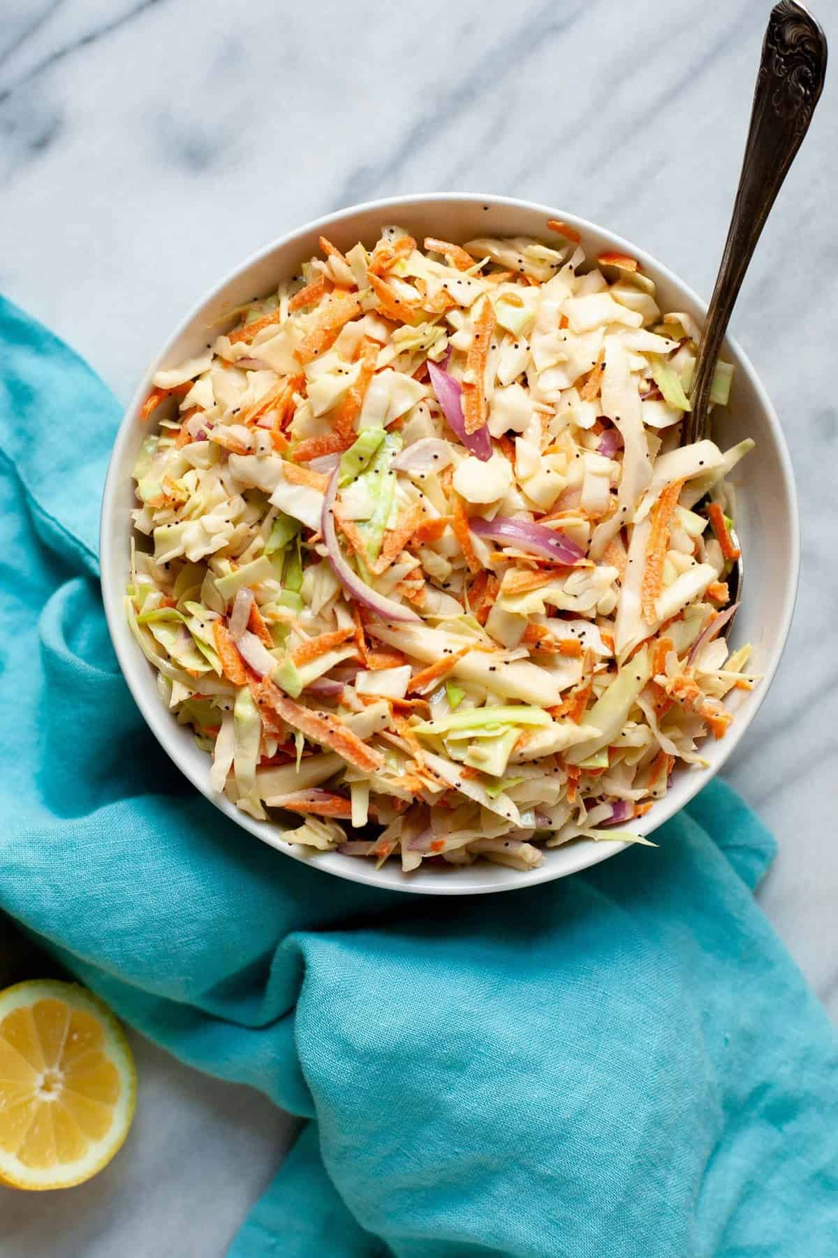 Overhead shot of Sweet and Creamy Coleslaw in a white bowl on top of a blue towel