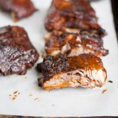 Close up side angle shot of Slow Cooker Barbecue Ribs on a white background