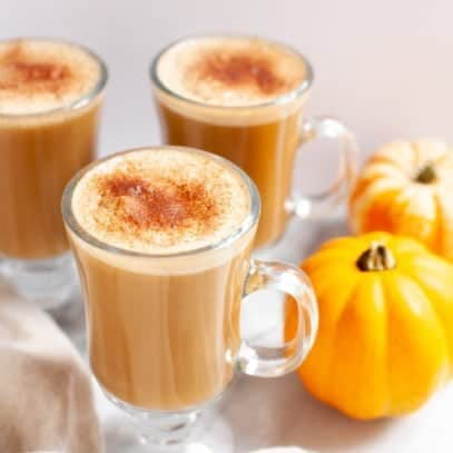 Three glass mugs filled with vegan pumpkin spice lattes and topped with cinnamon, with mini pumpkins nearby