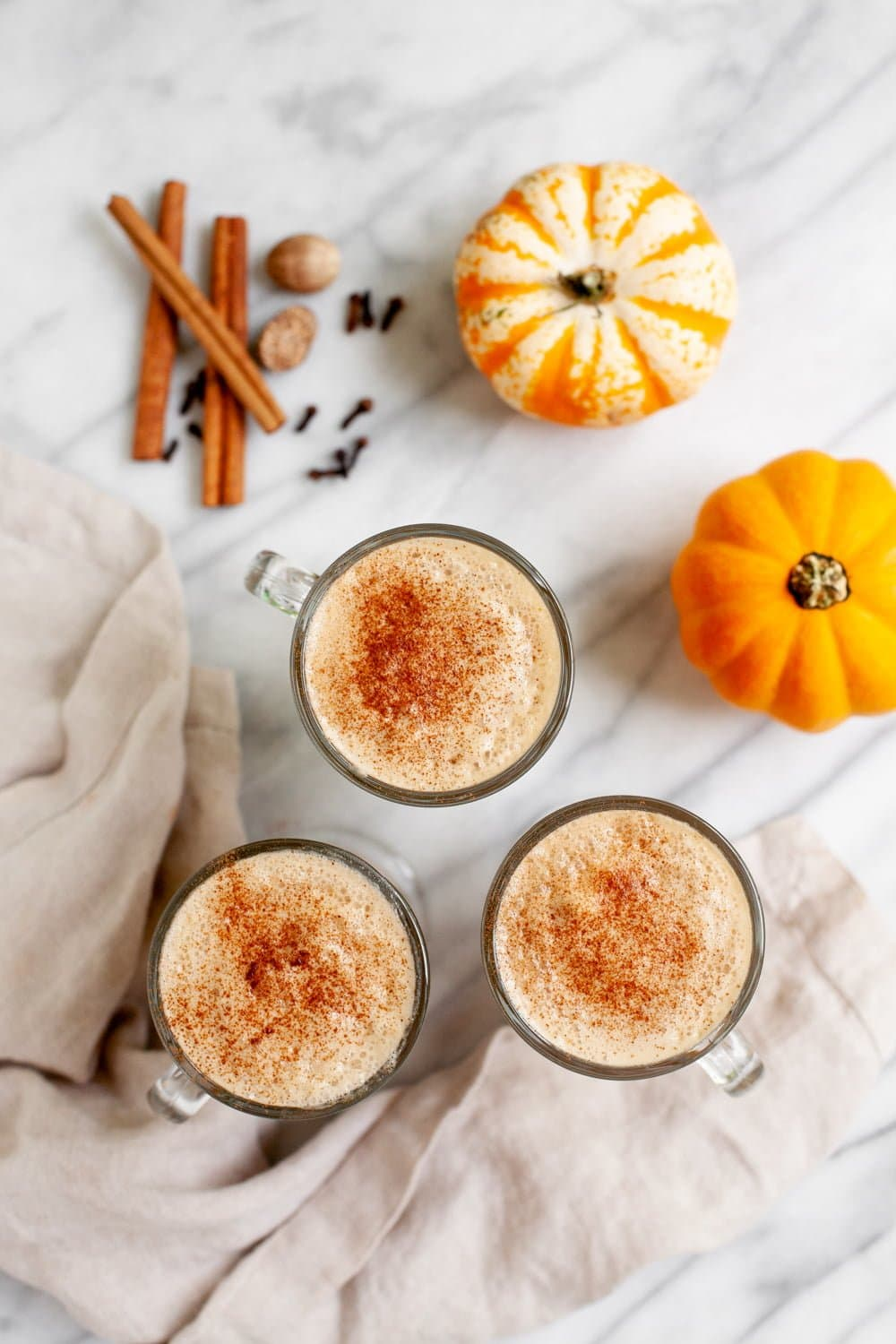 Overhead shot of three glass mugs filled with vegan pumpkin spice lattes and topped with cinnamon, with whole spices mini pumpkins nearby