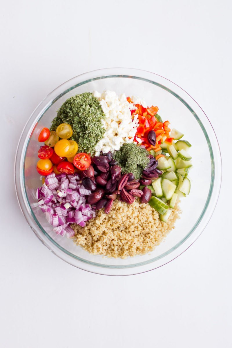 Overhead shot of the ingredients for Greek Quinoa Salad in a glass bowl