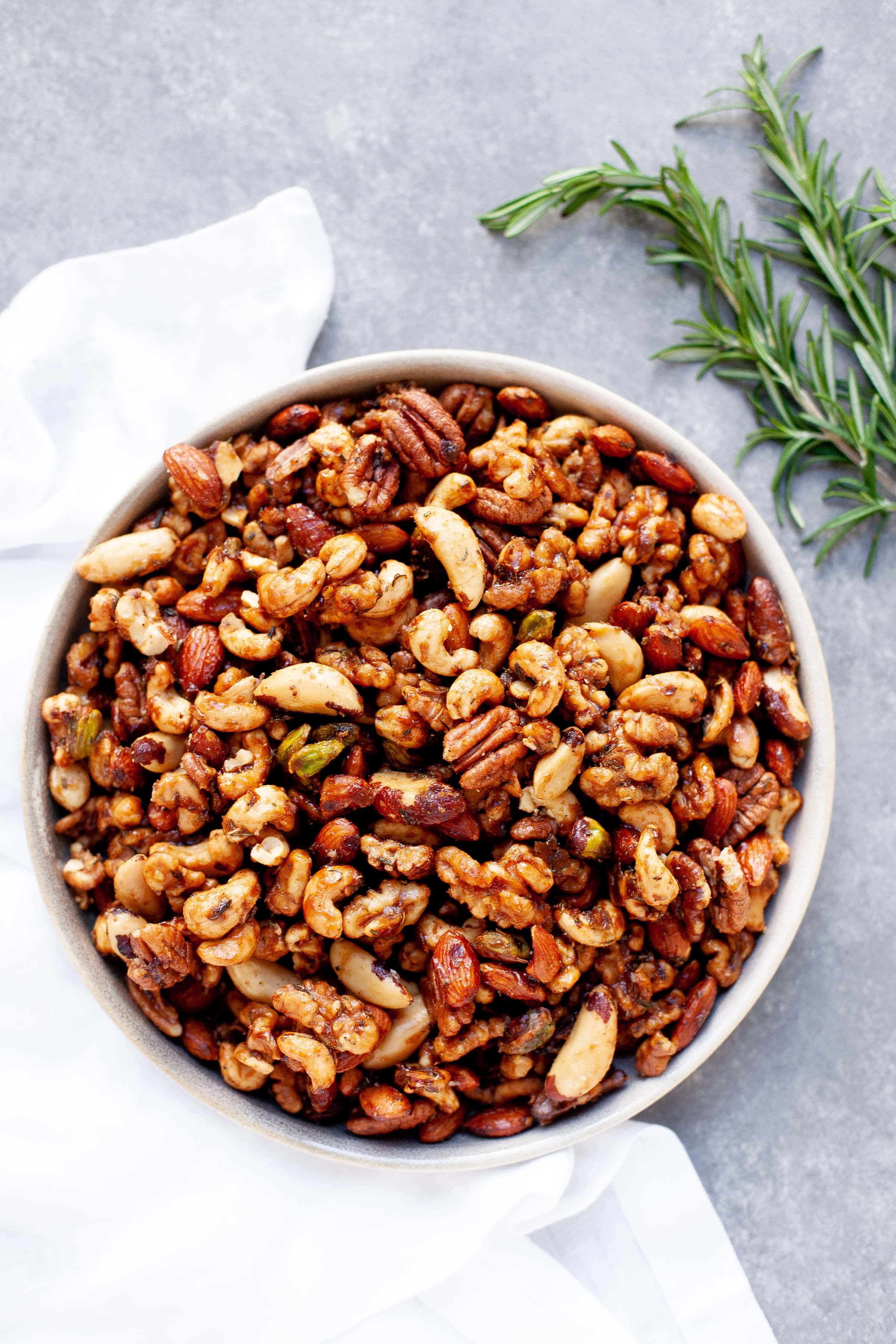 White bowl full of Maple Rosemary Bar Nuts, with sprigs of rosemary nearby