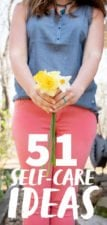 Shoulders-down shot of a woman in a blue shirt and pink pants, holding a bunch of daffodils, with a text overlay