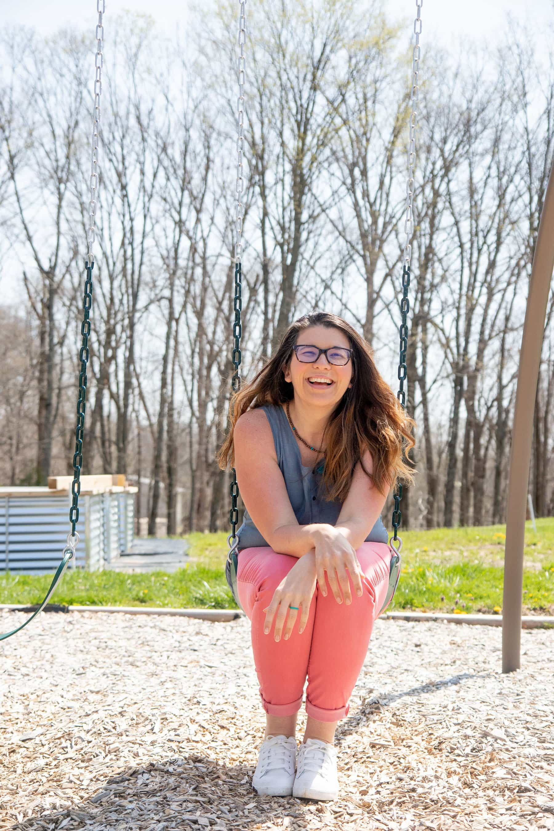 Woman sitting on a swing outside, smiling
