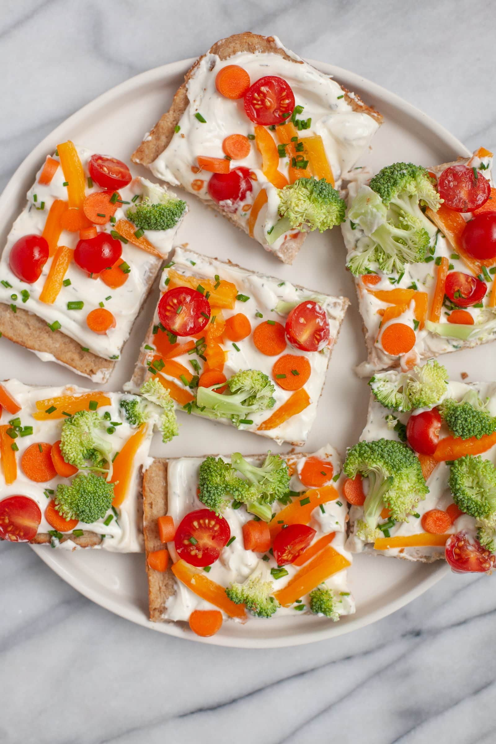 Off-white plate of Cold Veggie Pizza Appetizers cut into squares
