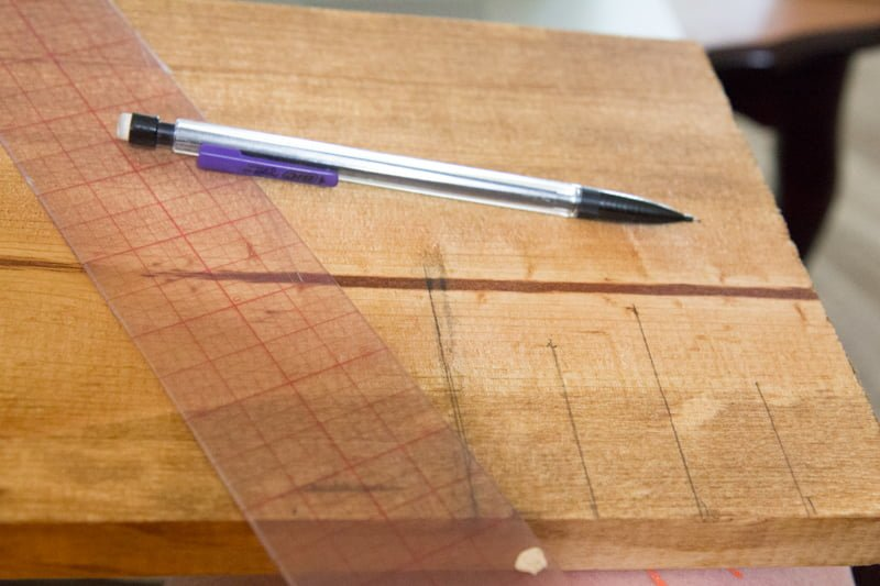 Mechanical pencil and a ruler resting on top of a wooden board, marking ruler ticks.
