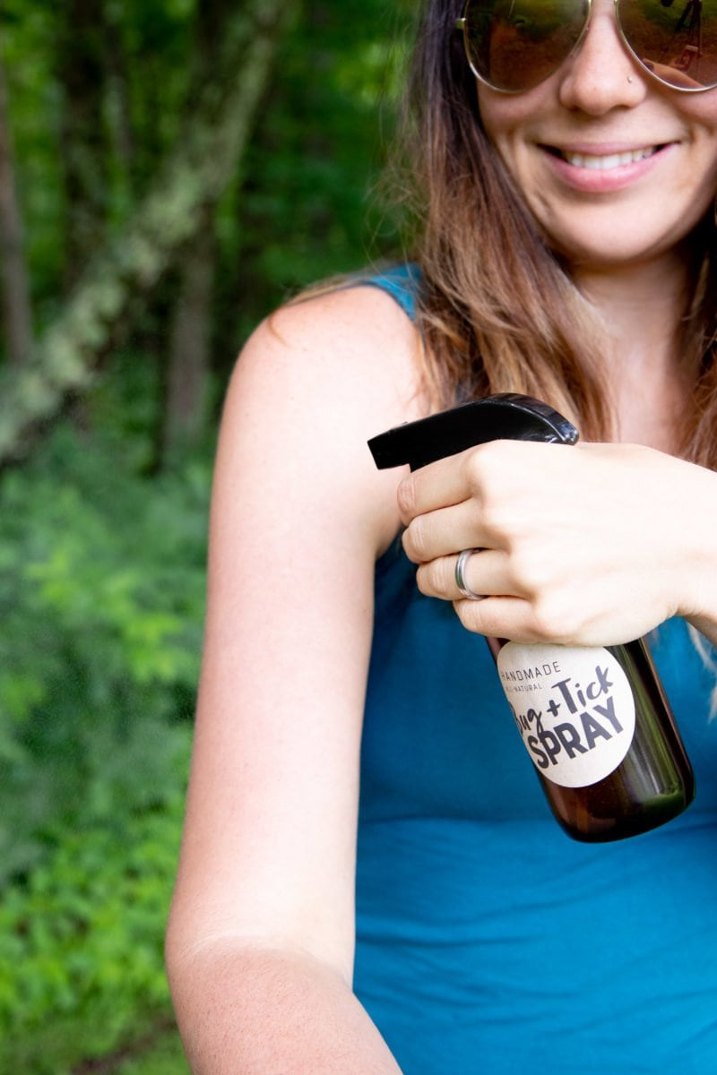 Woman spraying herself with an amber bottle of homemade all-natural tick and bug spray