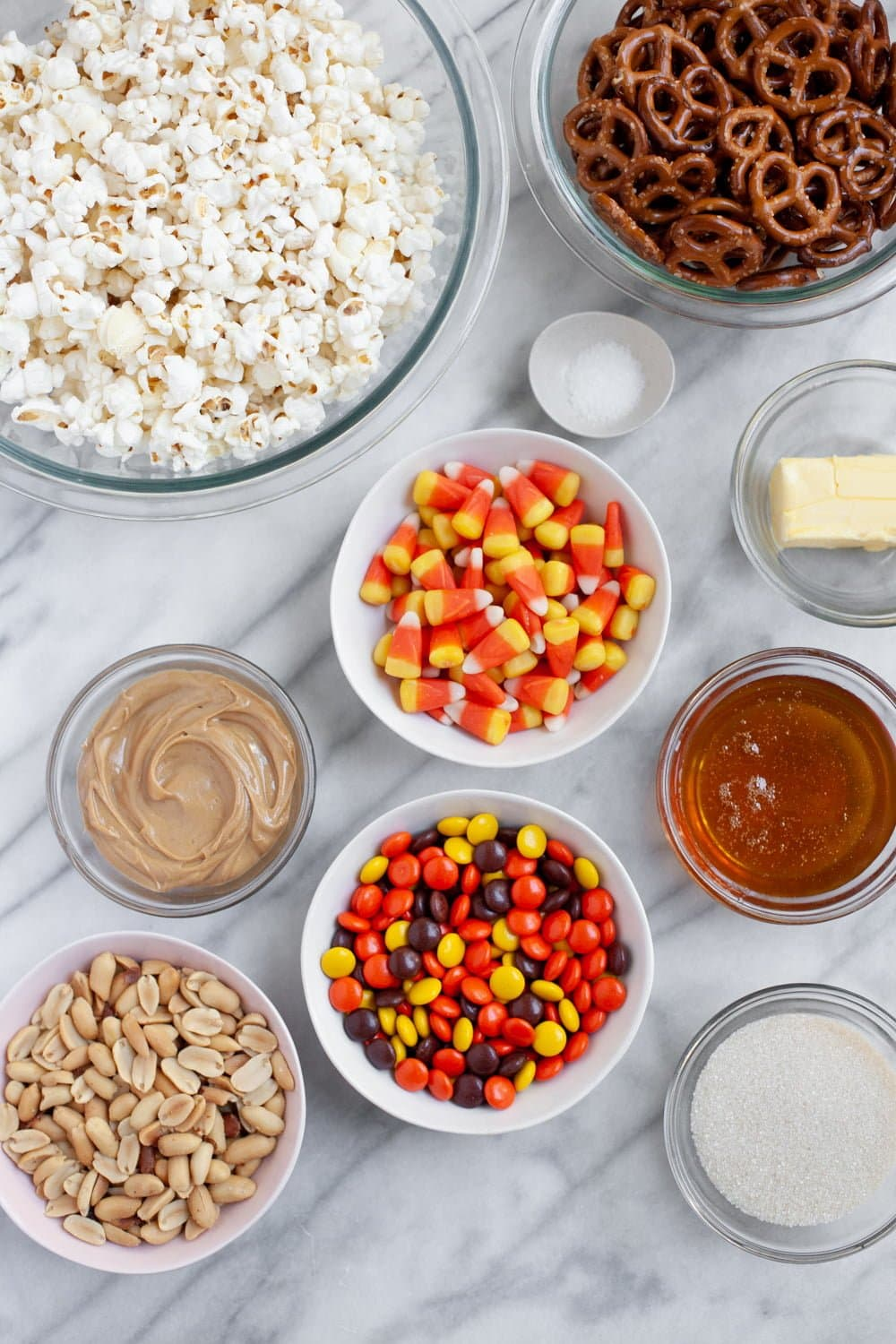 Ingredients for Peanut Butter Monster Munch Halloween Party Mix in individual bowls - popcorn, peanut butter, Reese's Pieces, candy corn