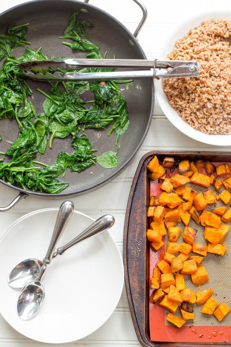 Components for Curried Sweet Potato Breakfast Bowls in individual pans - curried sweet potatoes, sauteed greens, and cooked farro