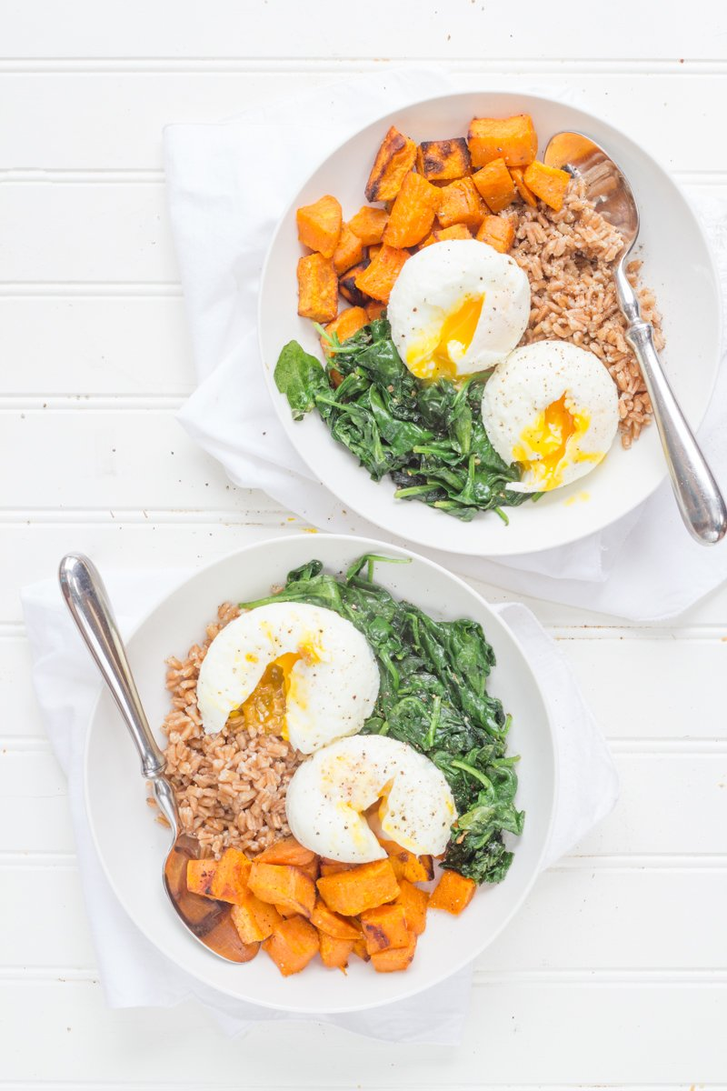 Curried Sweet Potato Breakfast Bowls on a white background, in white bowls and with silver spoons
