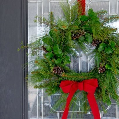 Evergreen wreath hanging from a red ribbon on a front door.