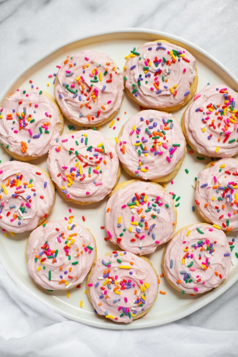 Lofthouse Sugar Cookies with pink icing and rainbow sprinkles on a plate