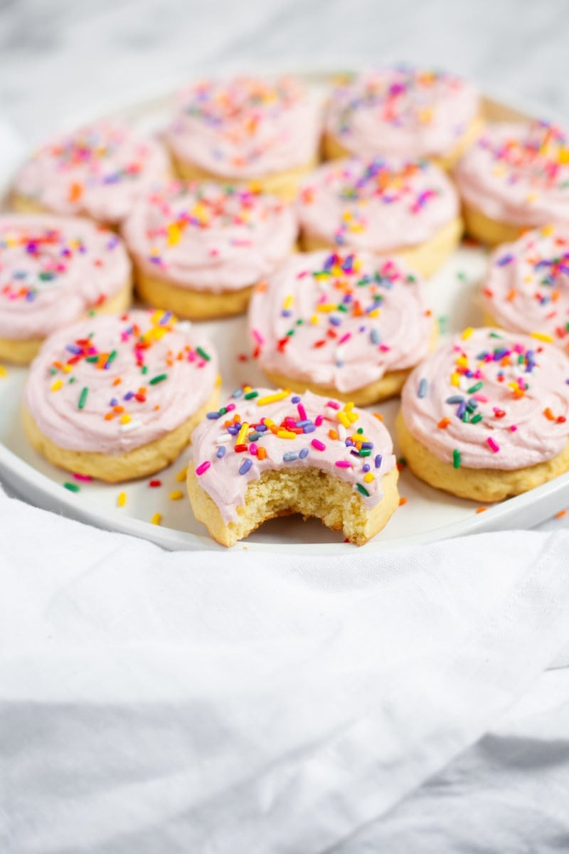 Lofthouse Sugar Cookies with pink frosting and rainbow sprinkles on a plate, with one cookie missing a bite