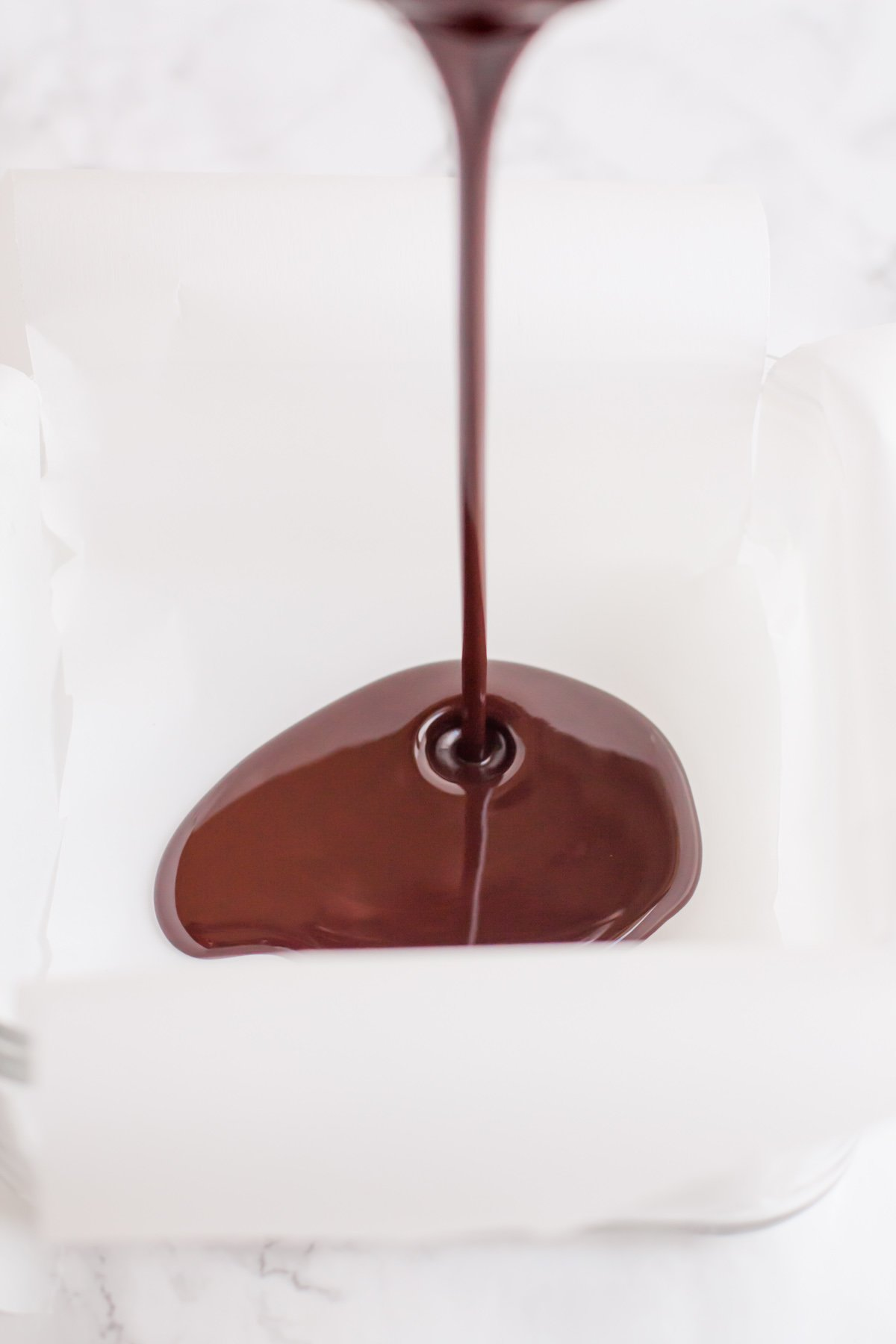 Melted coconut oil and cocoa powder being poured into a parchment paper-lined pan.
