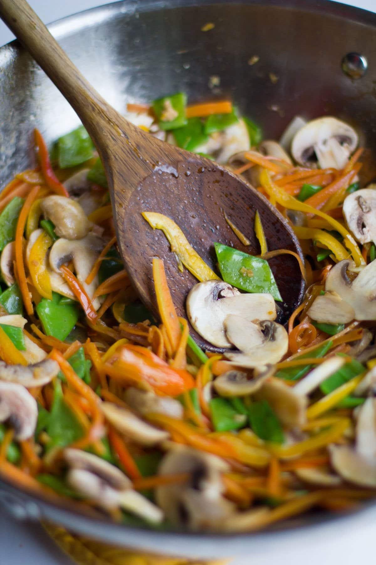 Wooden spoon stirring vegetables in a pan