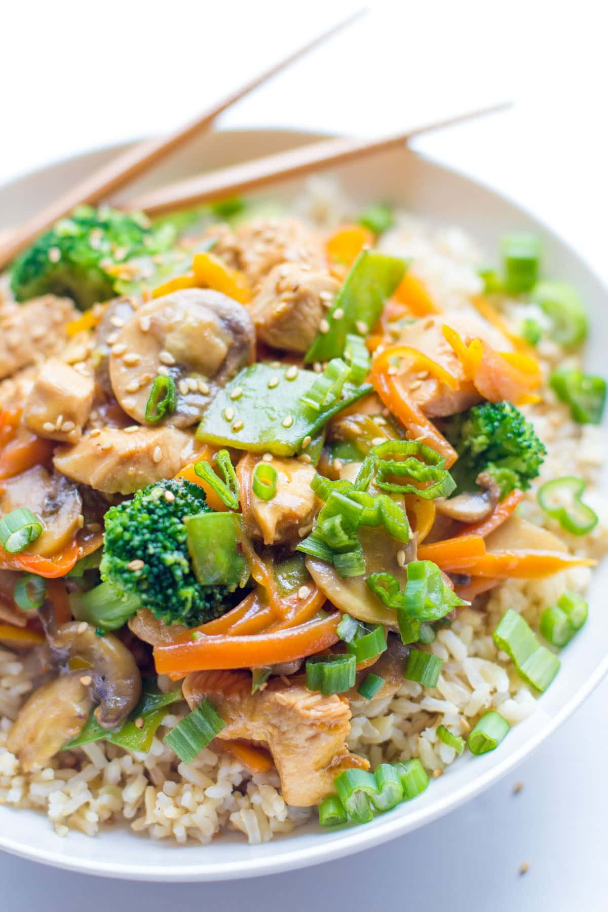 Healthy Chicken Stir Fry on top of brown rice in a white bowl on a white background
