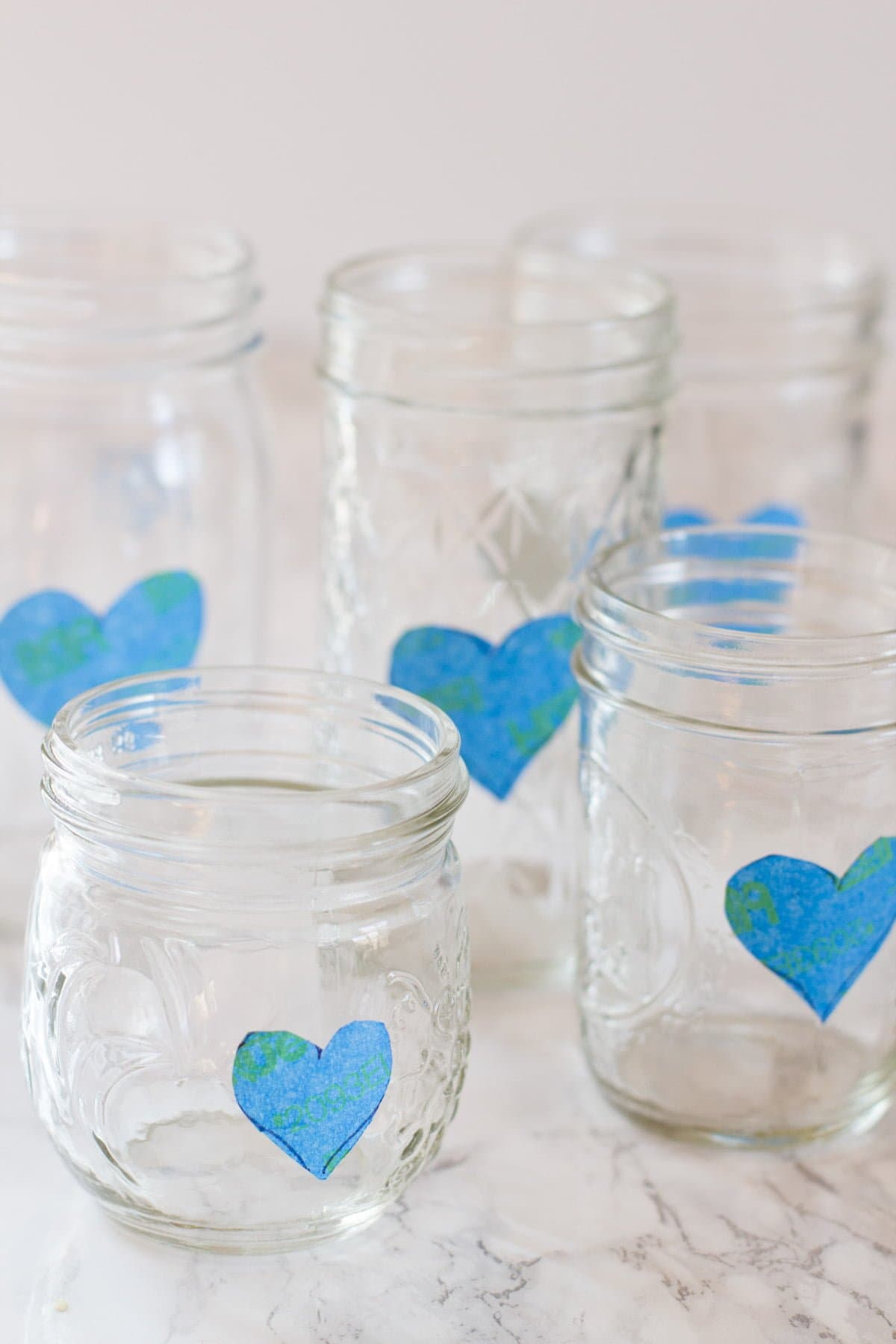 Cluster of mason jars, each with a heart made of painter's tape on the side