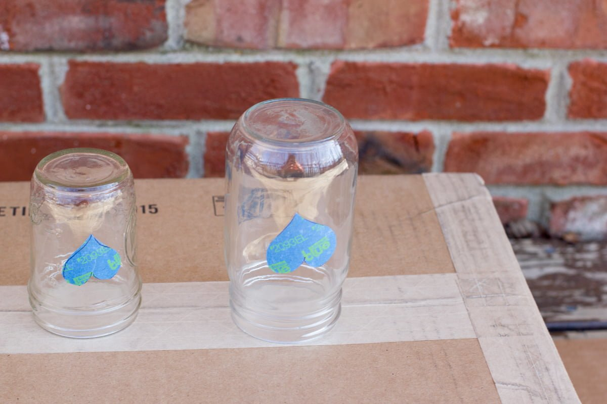 Two mason jars with painter's tape hearts sitting upside down on a piece of cardboard