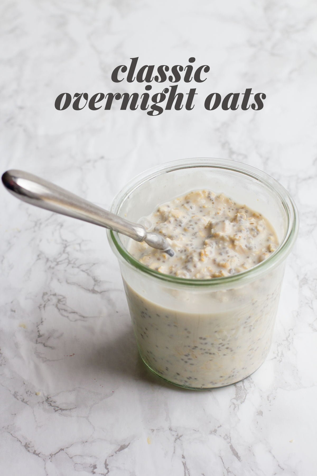 "A clear glass jar filled with overnight oats, with a spoon sticking out. A text overlay reads ""Classic Overnight Oats."""