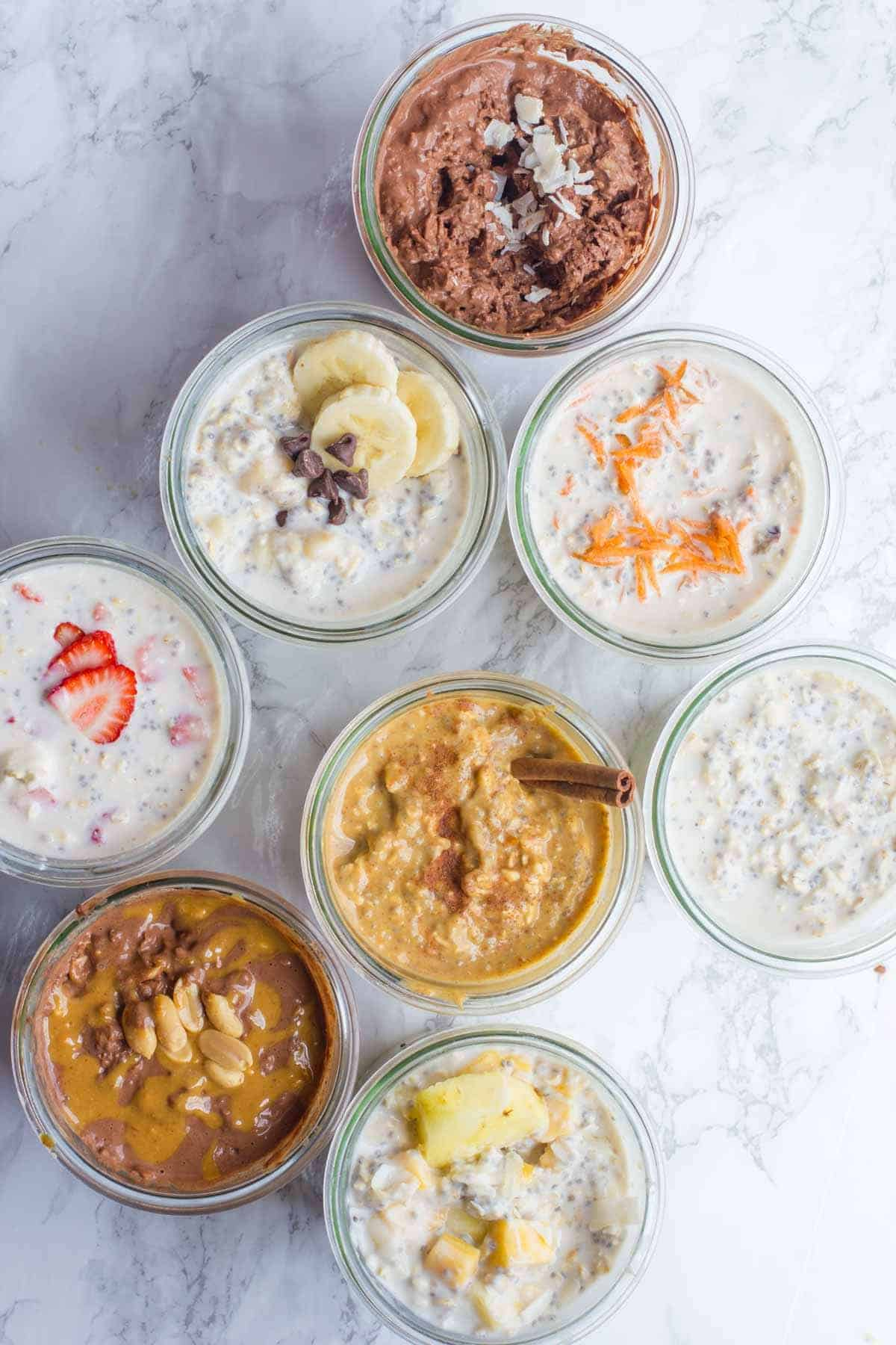 Overhead shot of eight different flavors of overnight oats, each in its own glass jar.