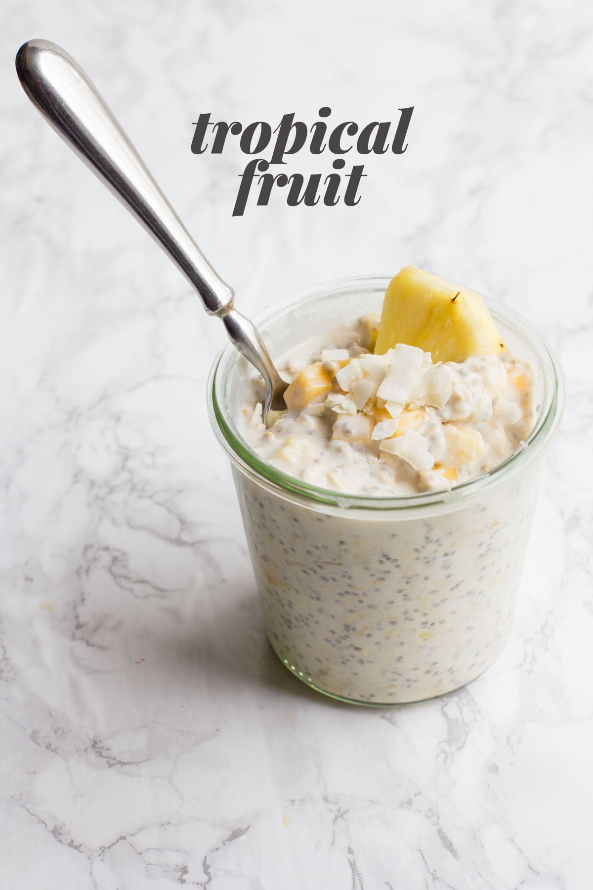 "A clear glass jar filled with Tropical Fruit Overnight Oats, with a spoon sticking out. A text overlay reads ""Tropical Fruit."""