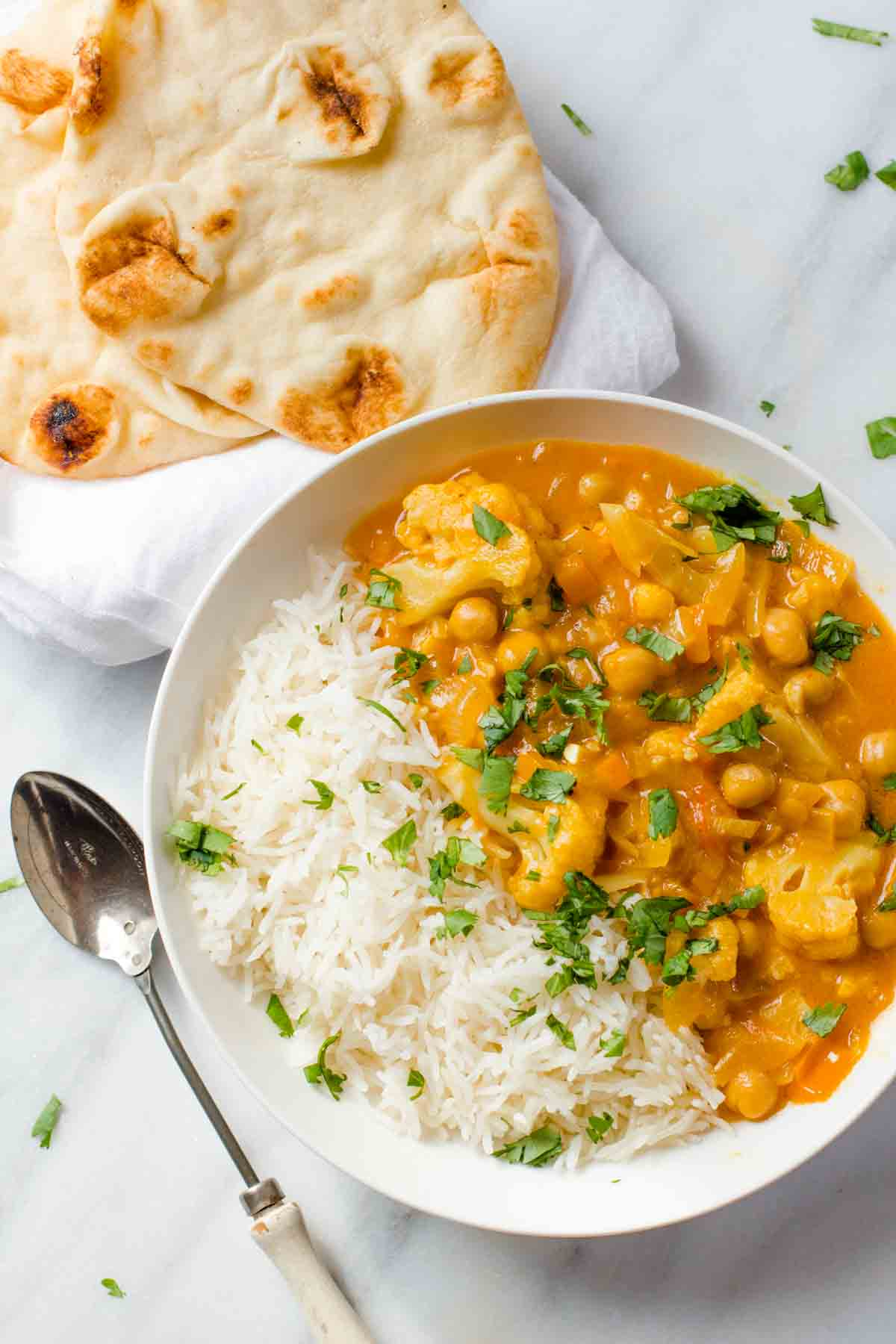 Cauliflower and Chickpea Curry in a white bowl with rice, with a spoon nearby