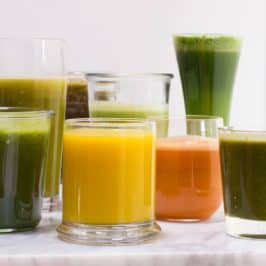 Glasses of varying heights filled with fruit and vegetable juices.