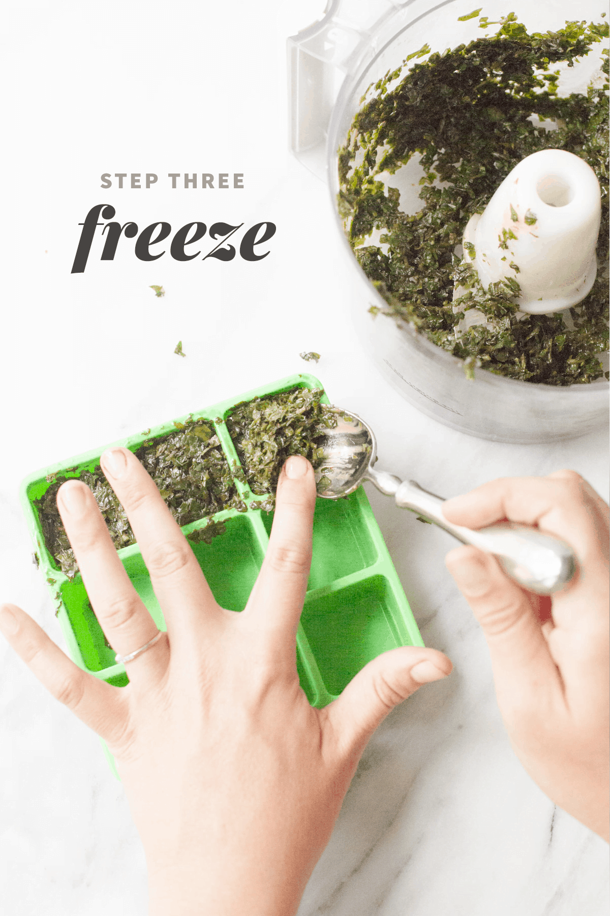 """Hands spoon fresh basil pureed with olive oil out of a food processor and into an herb freezing tray. A text overlay reads """"Step Three: Freeze."""""""