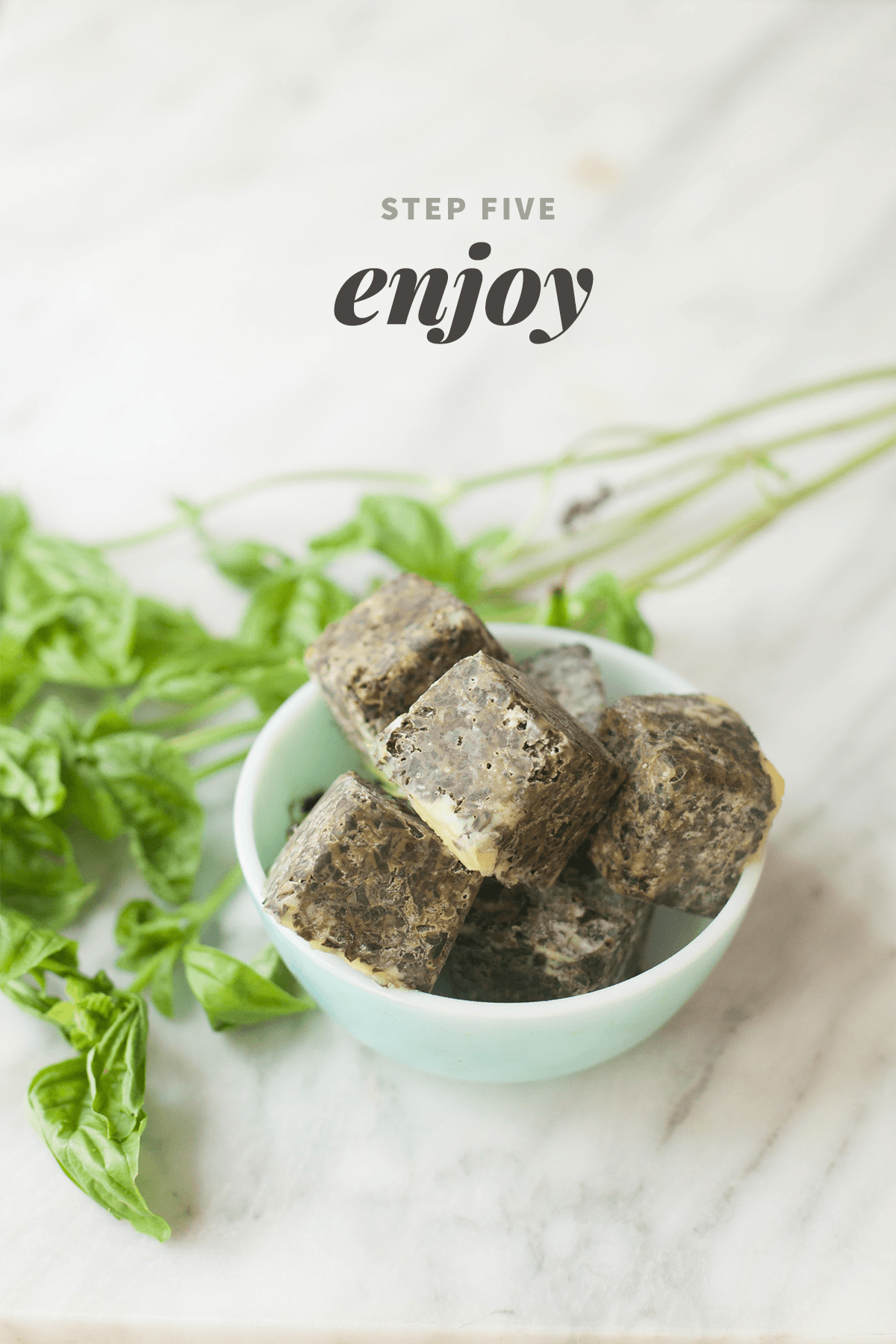 """Frozen cubes of basil in a small bowl, next to some stems of fresh basil. A text overlay reads """"Step Five: Enjoy."""""""