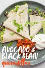 "Quesadilla triangles on a gray plate, with a mound of salsa and a mound of sour cream next to them. A text overlay reads ""Avocado and Black Bean Quesadillas."""