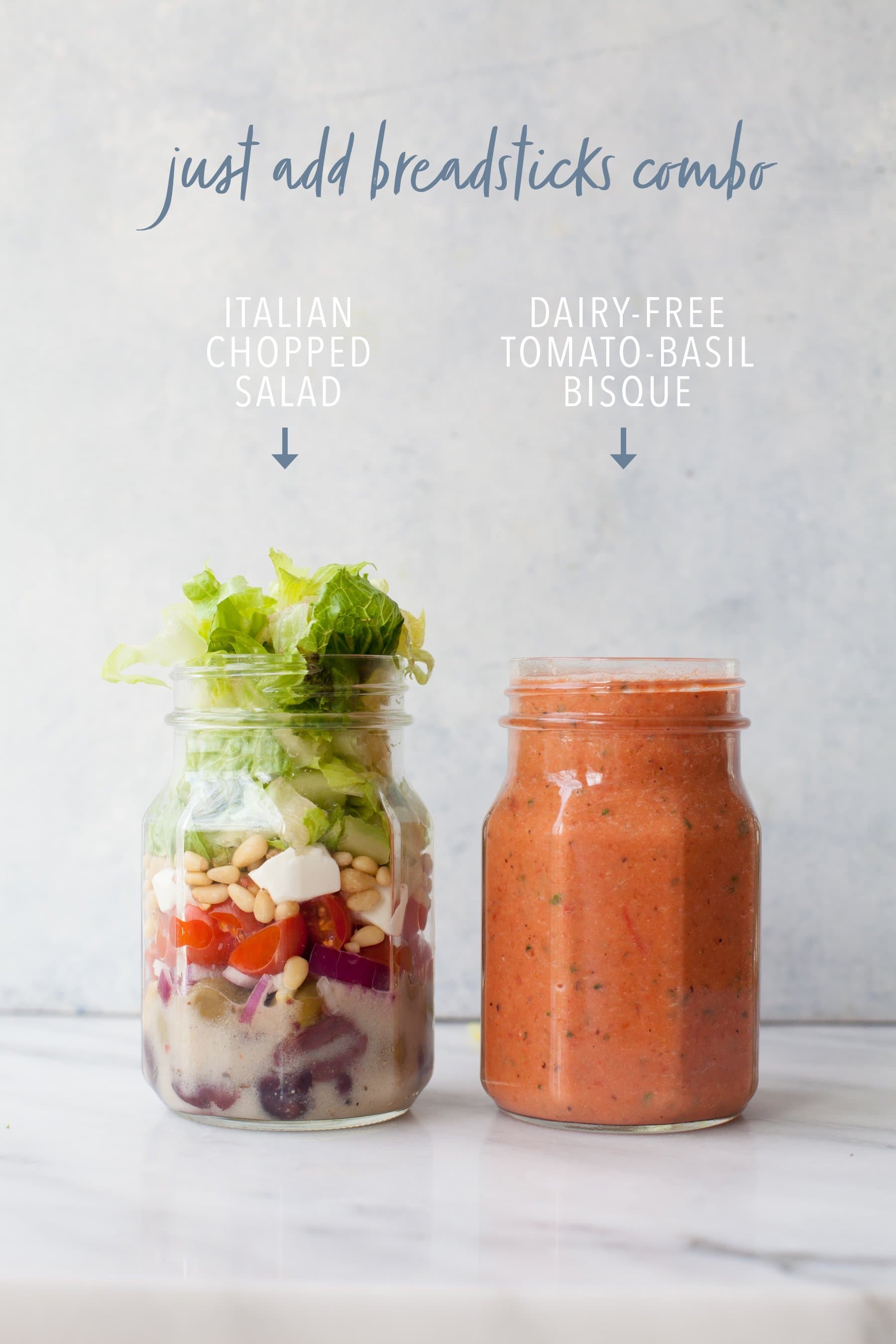 Two canning jars on gray background, one with salad and one with soup