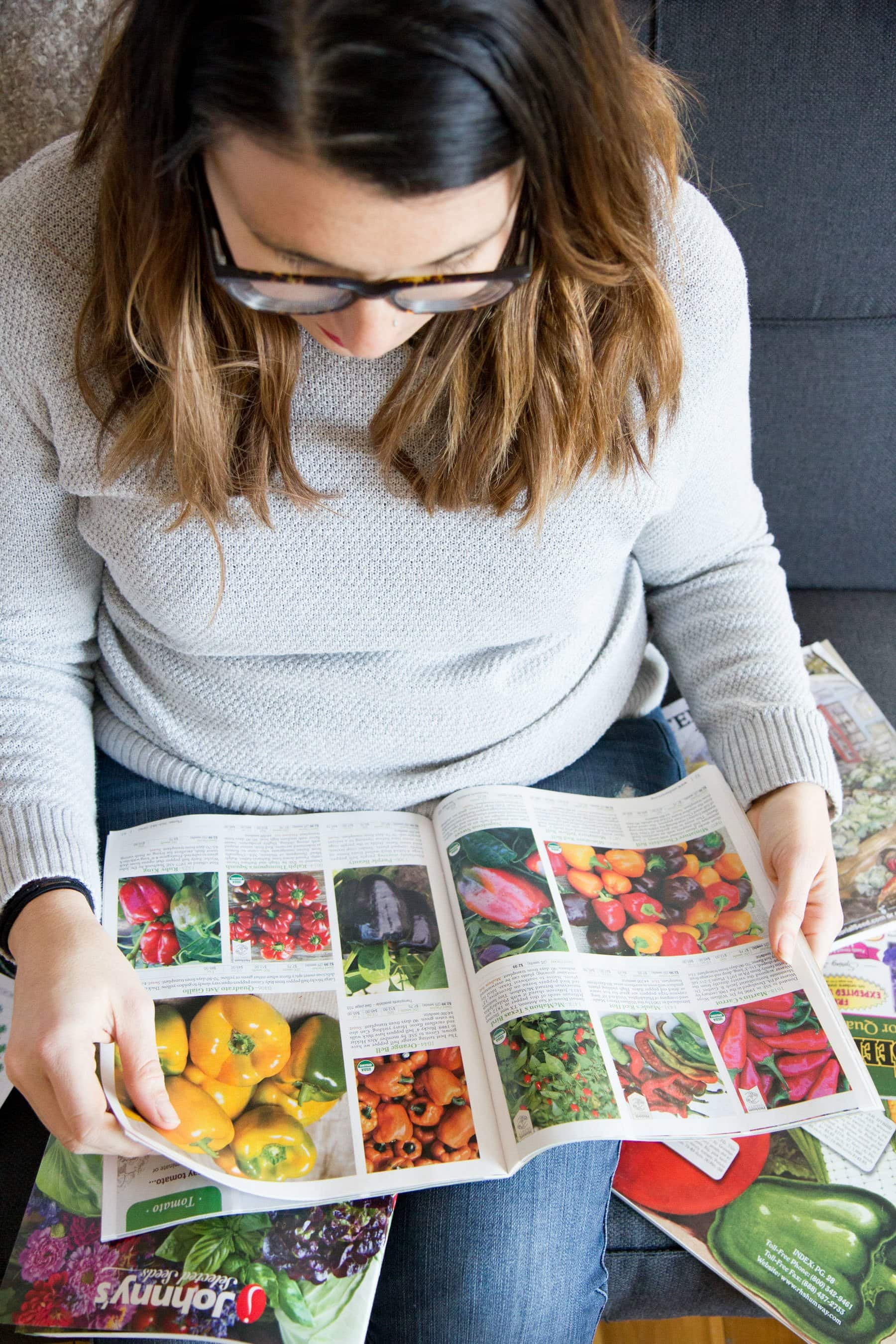 Woman sitting on couch looking through seed and gardening catalogs