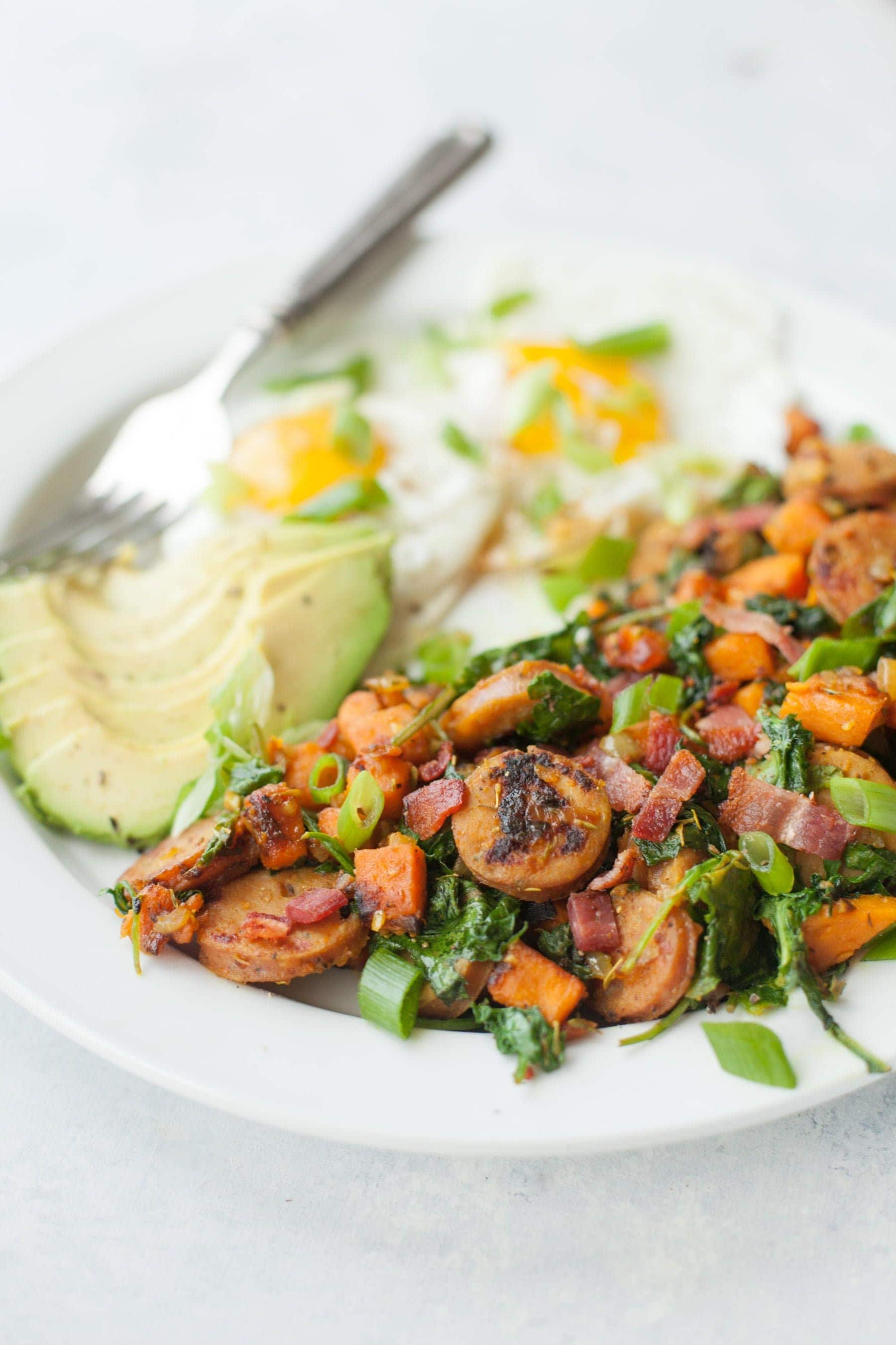 Tight view of white plate with sweet potato hash, eggs, and avocado