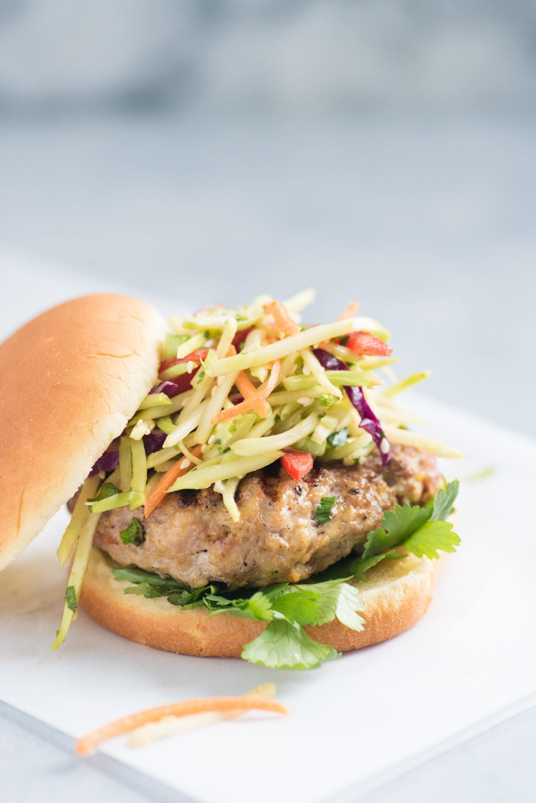 Close up side shot of Asian pork burger with broccoli slaw on top, served on a bun