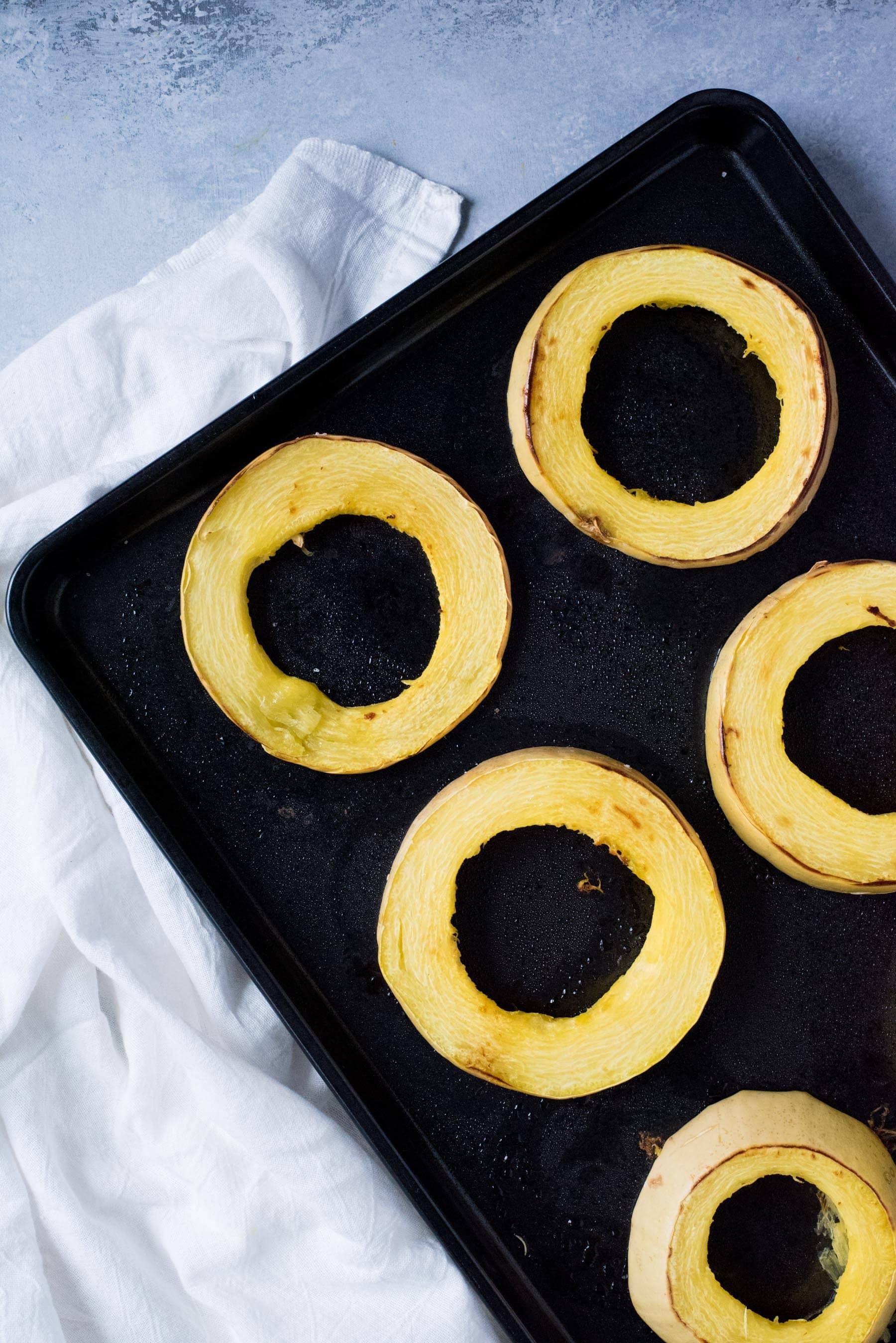 Overhead shot of rings of spaghetti squash on a dark baking pan