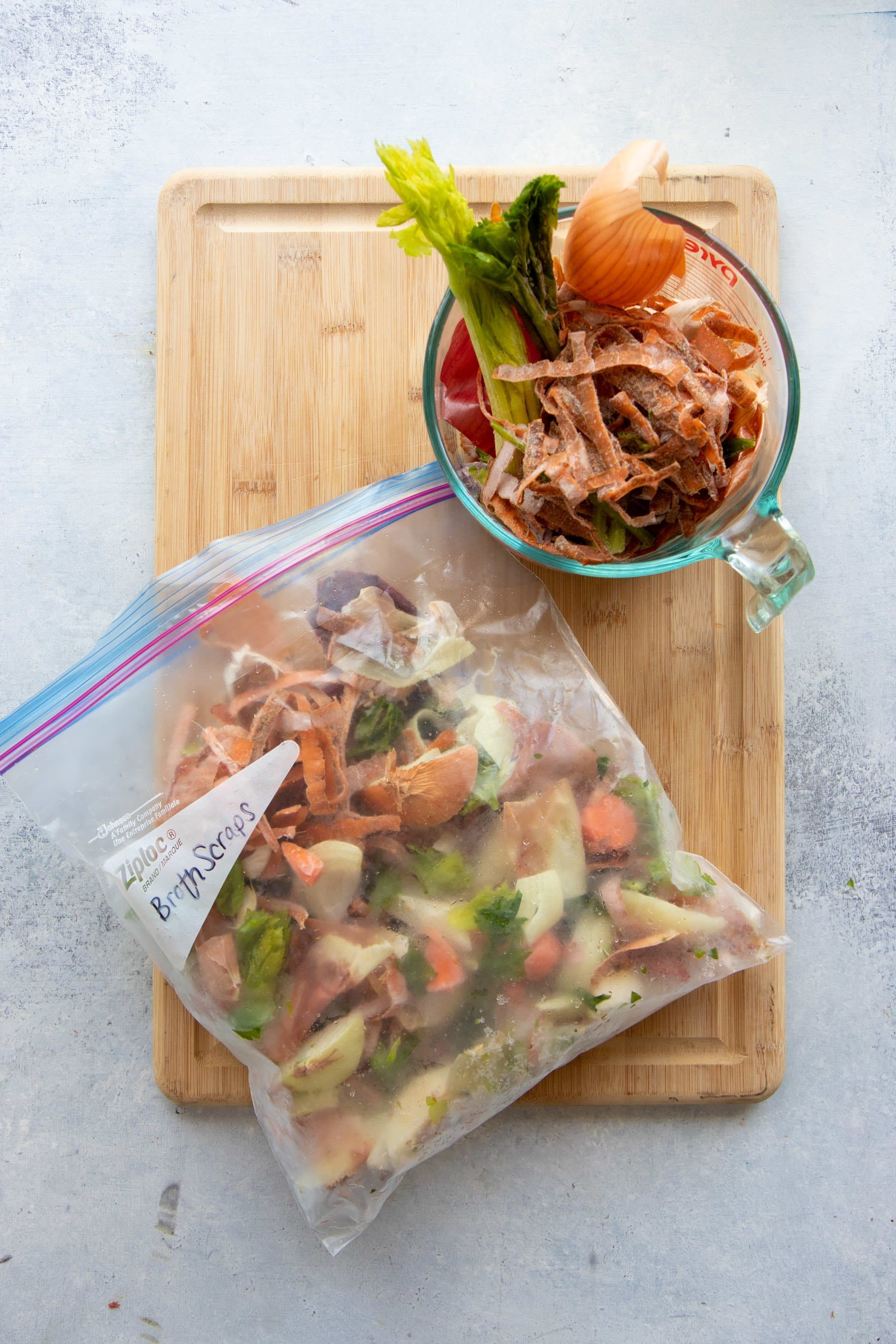 Overhead shot of veggie scraps for bone broth, in a glass measuring cup and in a freezer bag