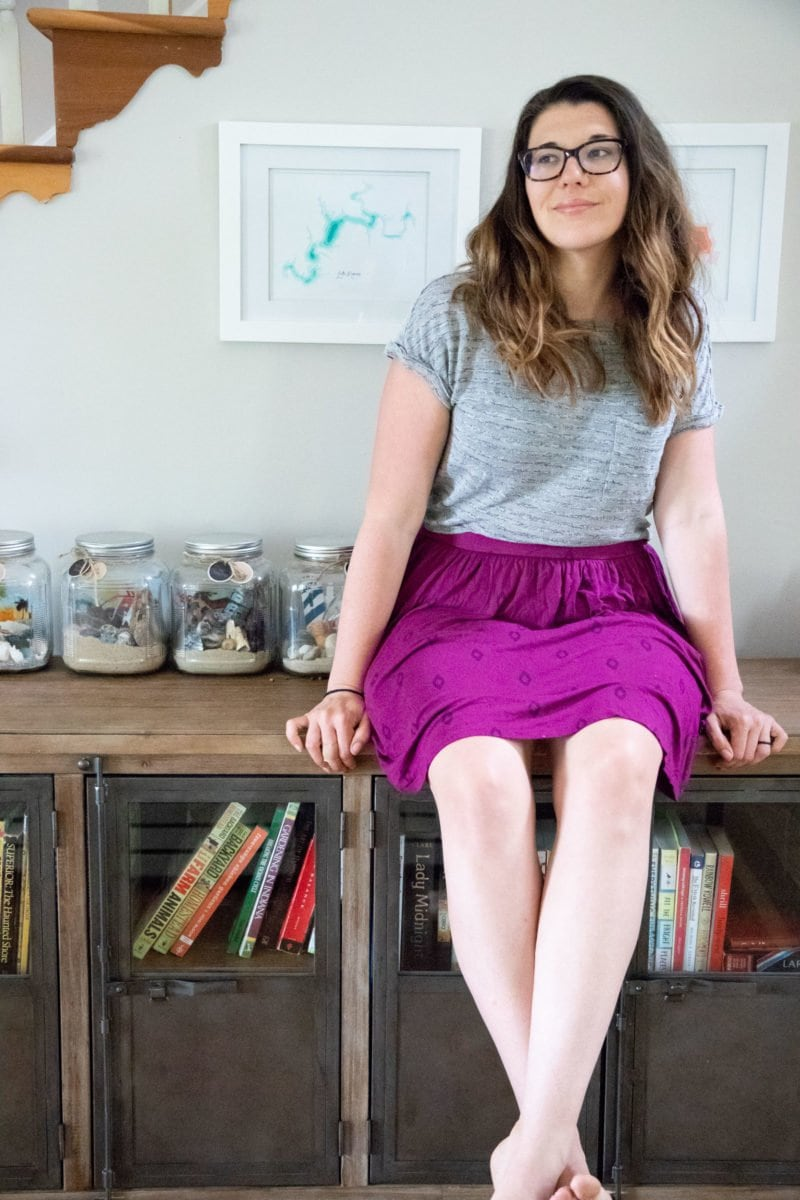 Woman in a gray shirt and purple skirt, sitting on a counter