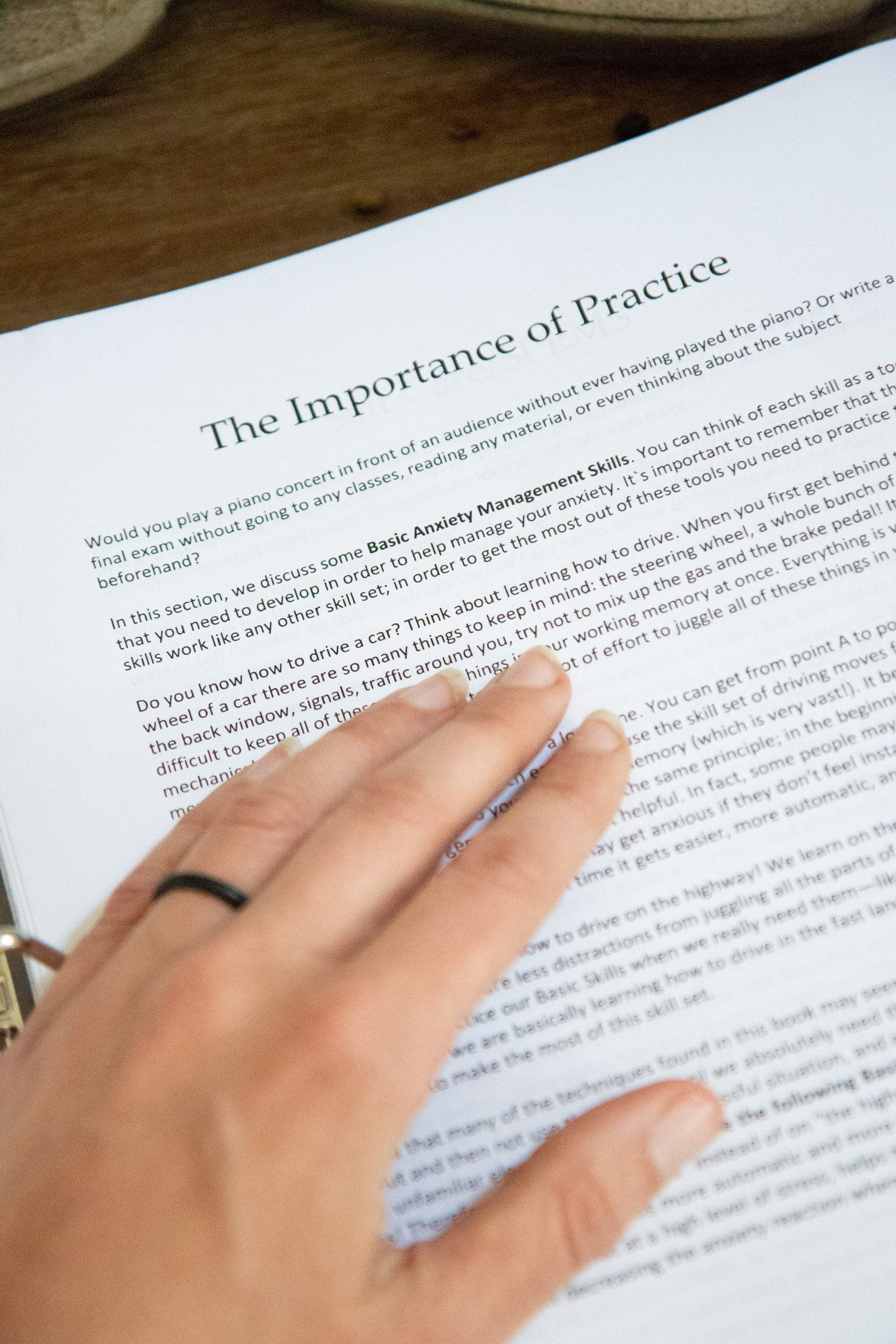 """Hand holding down a paper that says """"The Importance of Practice"""""""