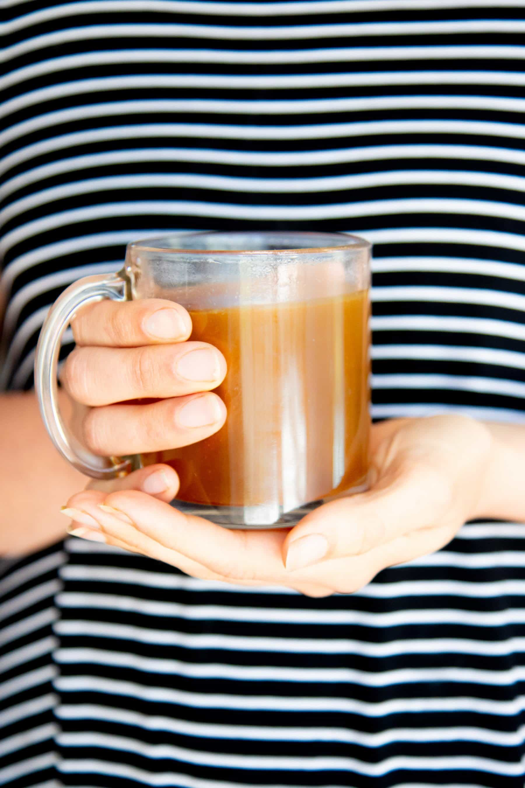 Clear mug of bone broth held in two hands