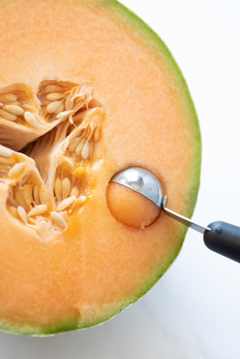 Overhead shot of halved cantaloupe being portioned out by a melon baller