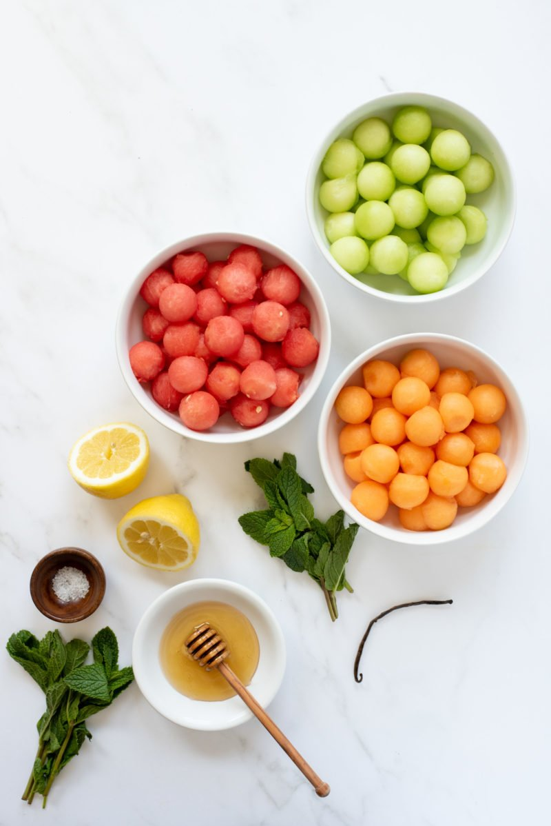 Overhead shot of ingredients for Honey-Mint Melon Salad, with each ingredient in its own white bowl