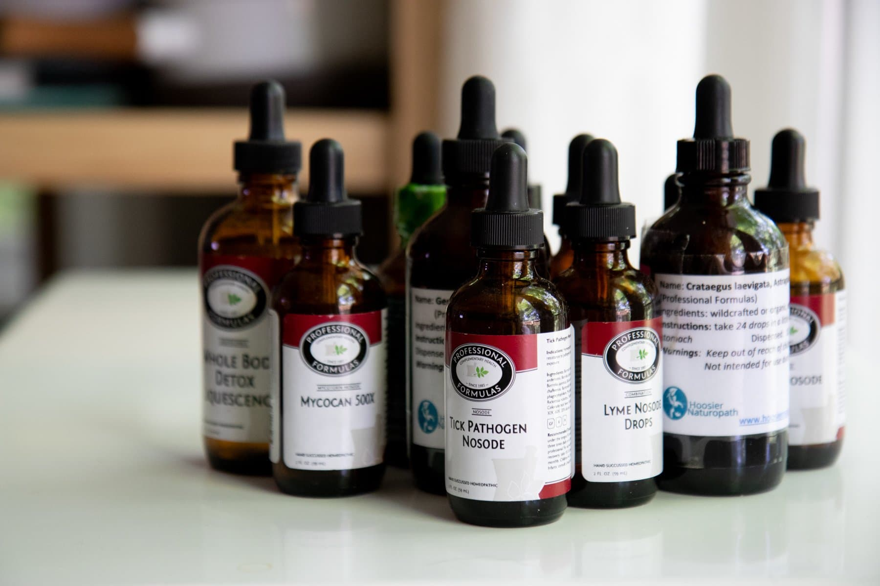 Cluster of eyedropper bottles containing herbal treatments for Lyme Disease