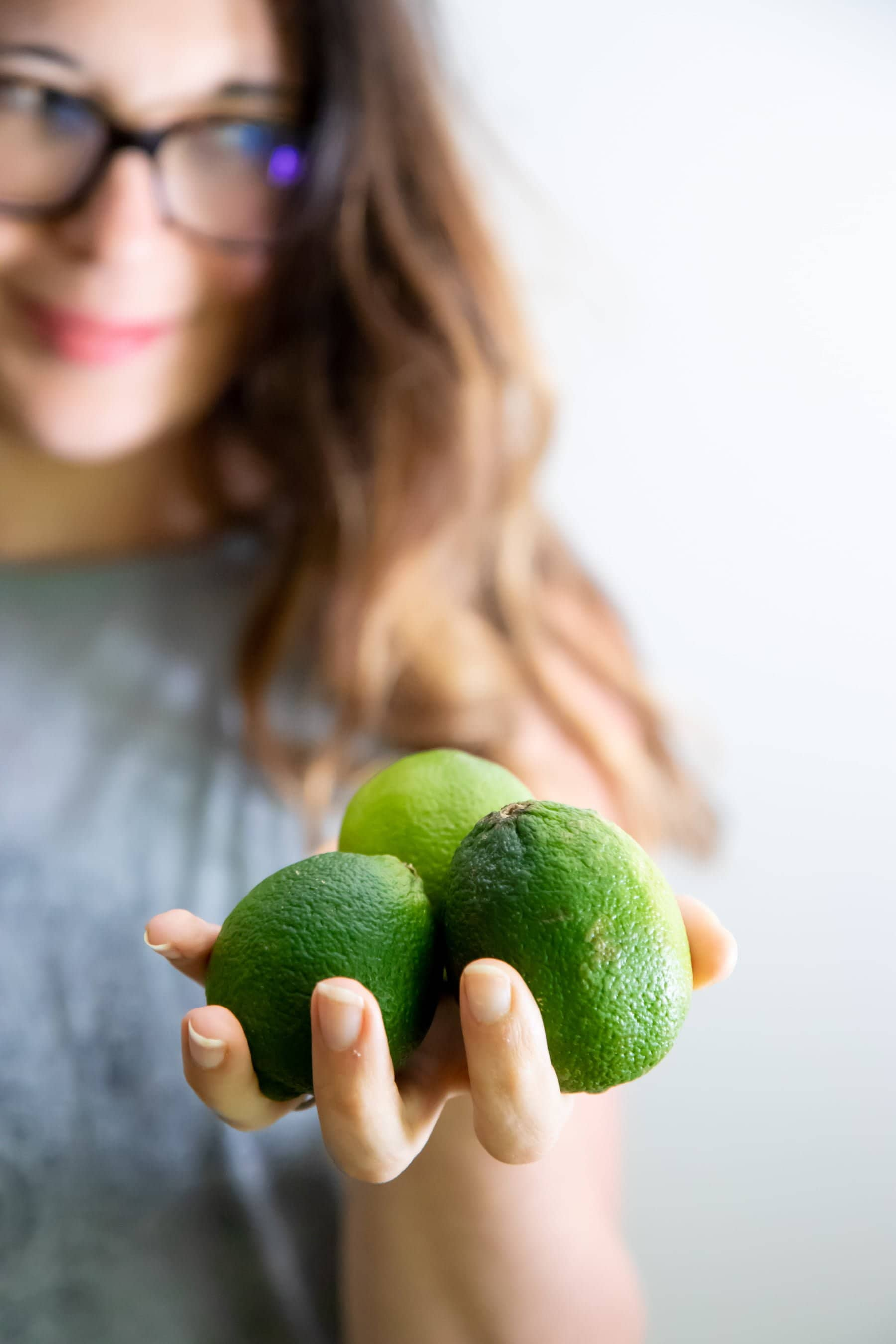 Woman holding out 3 limes in her palm